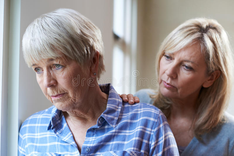 Mulher superior séria com filha adulta em casa foto de stock