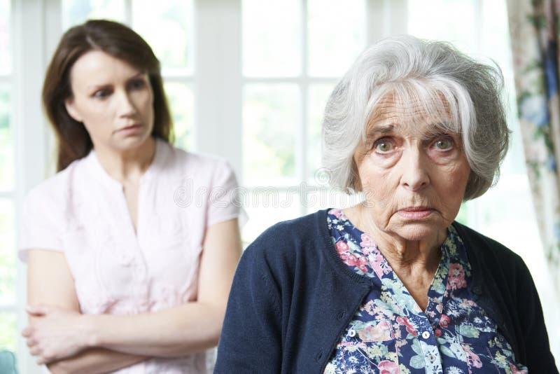 Mulher superior séria com a filha adulta preocupada em casa fotografia de stock