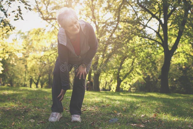 Mulher superior séria que tem a dor no joelho após o exercício fotos de stock