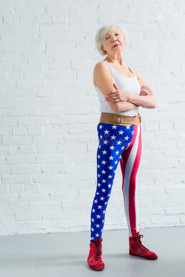 mulher superior segura no sportswear que está com braços cruzados e vista imagens de stock royalty free