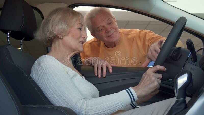 A mulher superior senta-se dentro do carro fotos de stock royalty free
