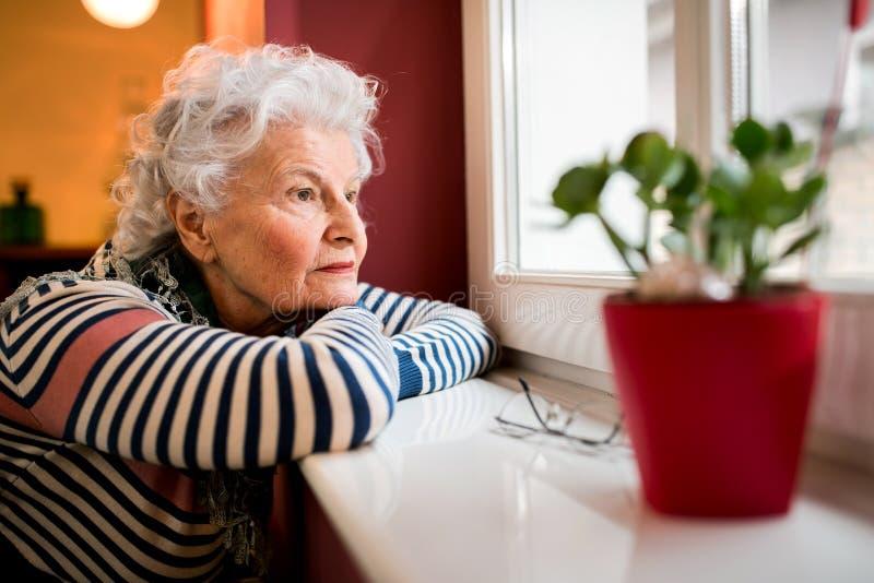Mulher superior sozinha triste que olha através da janela imagem de stock