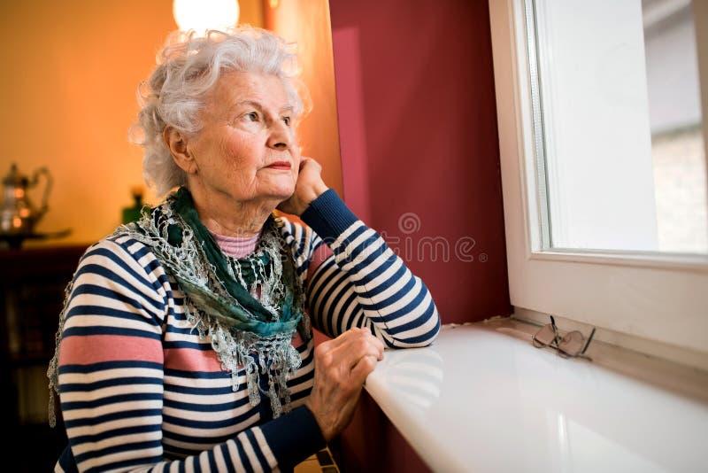 Mulher superior sozinha triste que olha através da janela em casa imagem de stock
