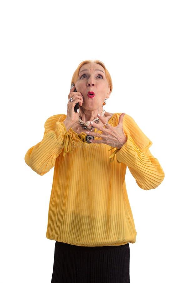 Mulher superior surpreendida com telefone celular imagens de stock