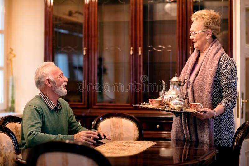 A mulher superior traz o serviço do chá a seu marido imagem de stock