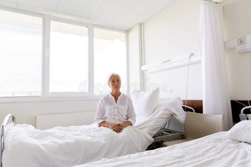Mulher superior triste que senta-se na cama na divisão de hospital foto de stock