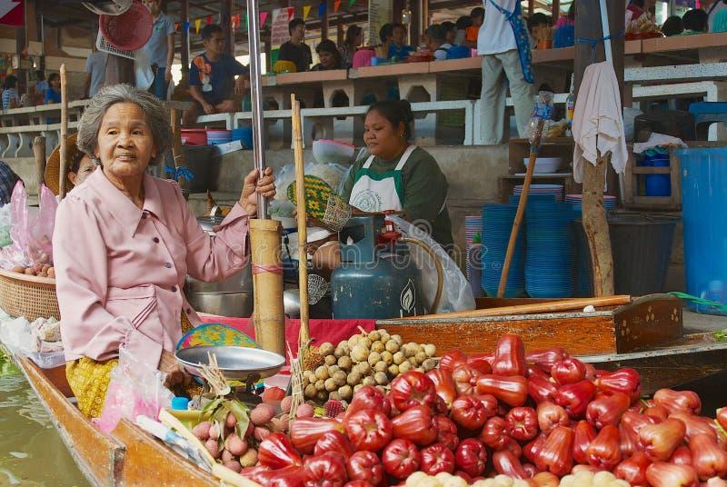 A mulher superior vende frutos dos barcos no mercado de flutuação em Damnoen Saduak, Tailândia imagens de stock