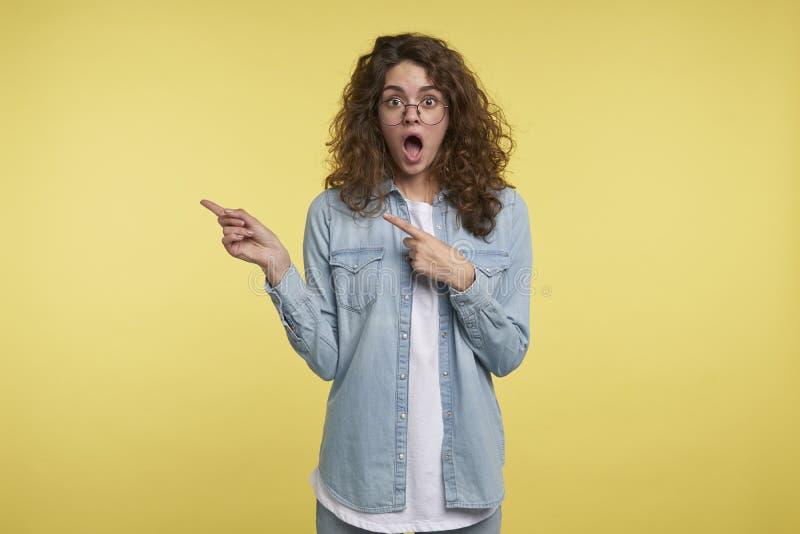 A mulher surpreendentemente feliz moreno com cabelo encaracolado mostra os dedos ao espaço vazio da cópia imagens de stock