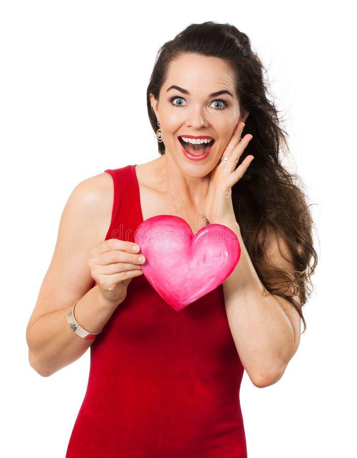 Mulher surpreendida bonita que guarda um coração do amor foto de stock