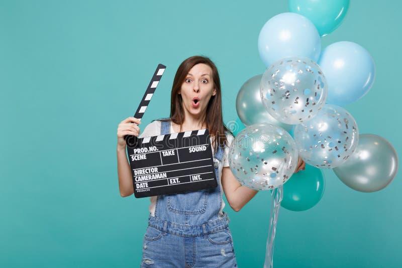 A mulher surpreendida com boca aberta guarda o clapperboard preto clássico da cinematografia que comemora com os balões de ar col foto de stock