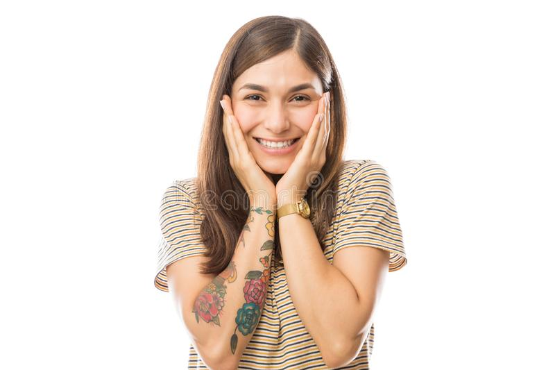 Mulher surpreendida com a cabeça nas mãos que sorri sobre o fundo branco fotos de stock