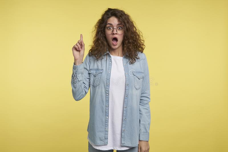 A mulher surpreendida com cabelo encaracolado aturdiu a expressão, apontando com indicador acima, veste monóculos e vestido fotografia de stock