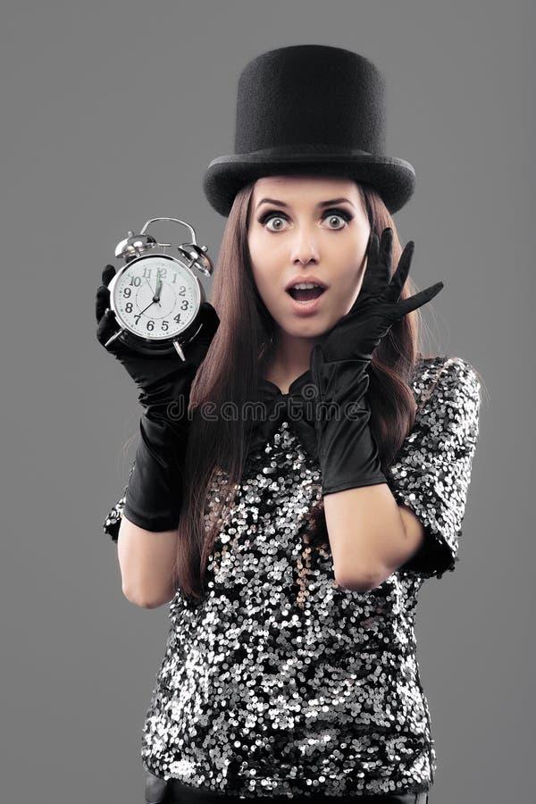 Mulher surpreendida com chapéu alto e despertador no ano novo fotografia de stock royalty free