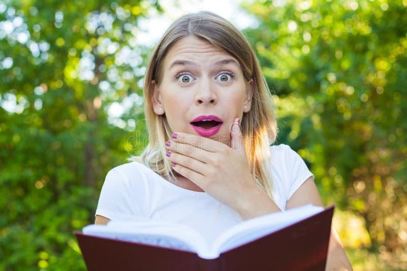 Mulher surpreendida com planeamento-livro imagem de stock royalty free