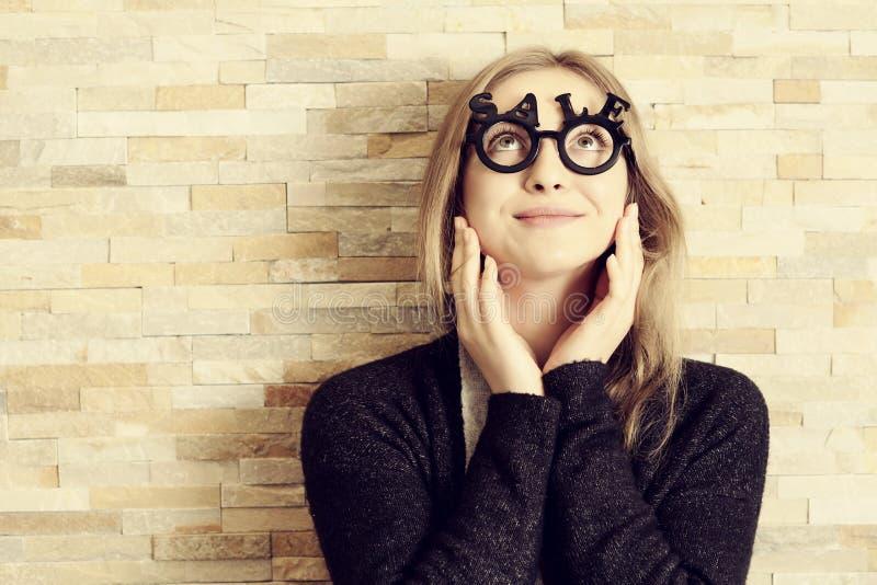 A mulher surpreendida com vidros deu forma no texto da VENDA fotos de stock