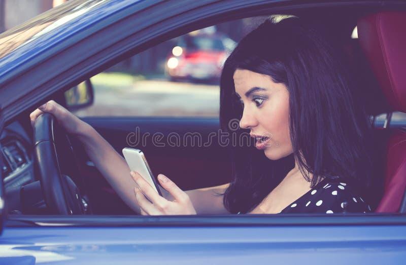 A mulher surpreendida confundiu a leitura de uma mensagem no telefone celular que conduz um carro imagens de stock