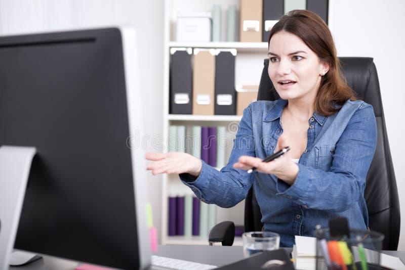 Mulher surpreendida do escritório em sua tabela com palmas acima imagem de stock royalty free