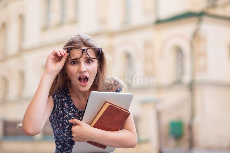 Mulher surpreendida do estudante que mant?m vidros com livros e PC foto de stock