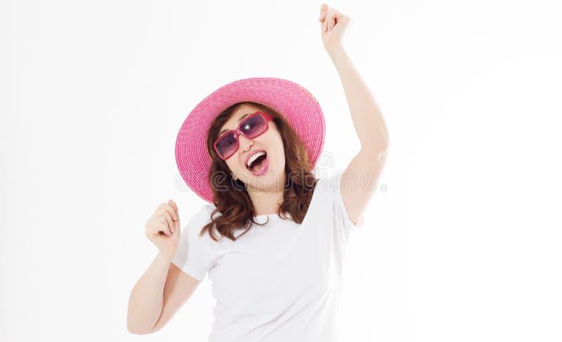 Mulher surpreendida e entusiasmado feliz no chap?u do ver?o, nos ?culos de sol e na camisa branca do molde t isolada no fundo bra fotos de stock