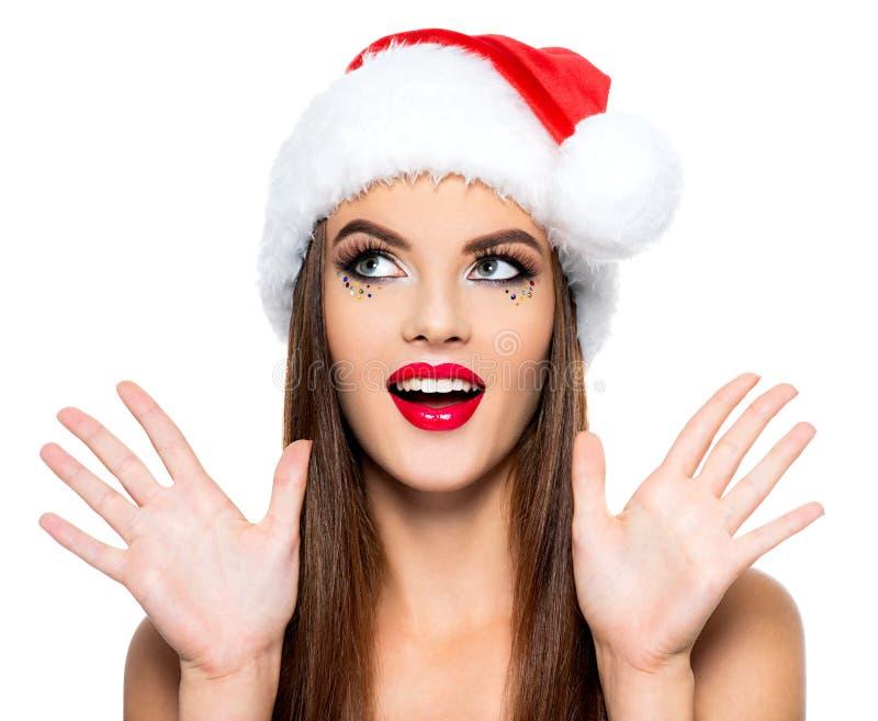 Mulher surpreendida em um chapéu de Santa A cara da mulher bonita com a composição criativa brilhante - isolada no fundo branco M imagens de stock royalty free