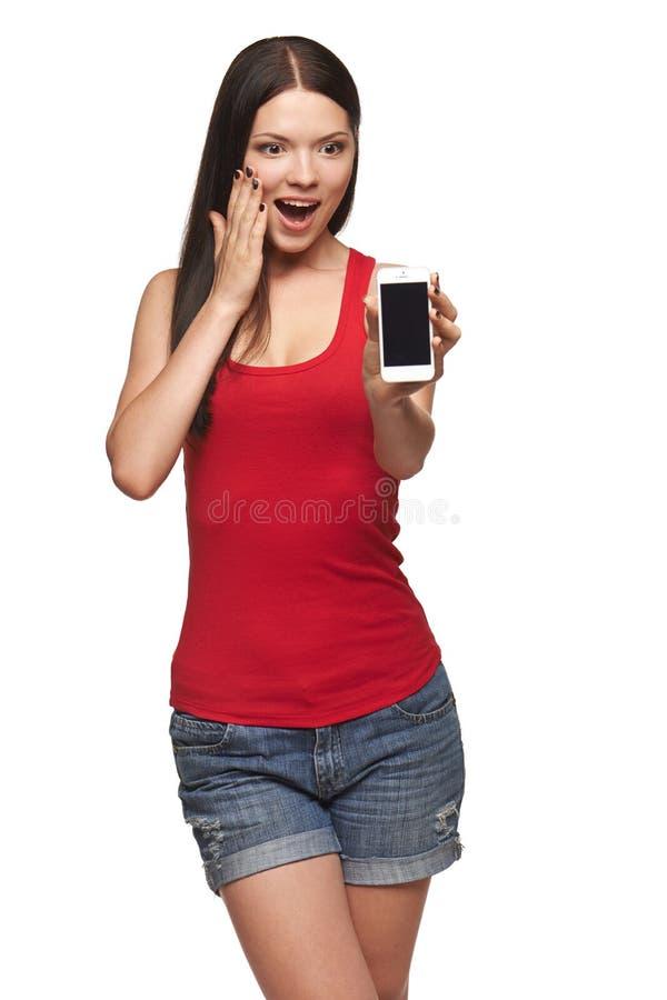 Mulher surpreendida entusiasmado que mostra o telefone celular fotografia de stock