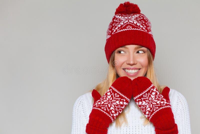Mulher surpreendida feliz bonita que olha lateralmente no excitamento Menina entusiasmado do Natal que veste o chapéu e mitenes m imagens de stock