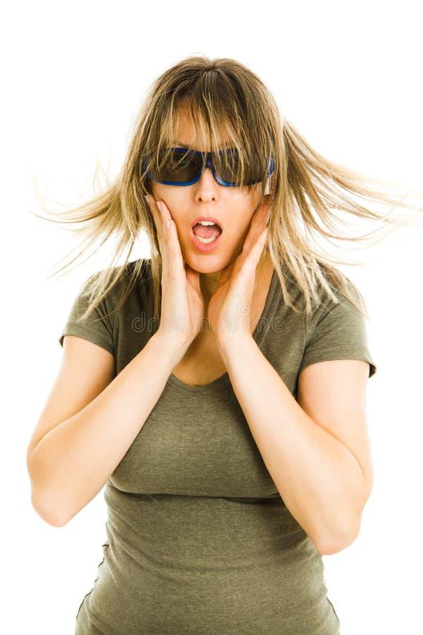 A mulher surpreendida no cinema que veste os vidros 3D que experimenta o cinema 5D efetua o filme de observação assustado - gesto imagem de stock royalty free