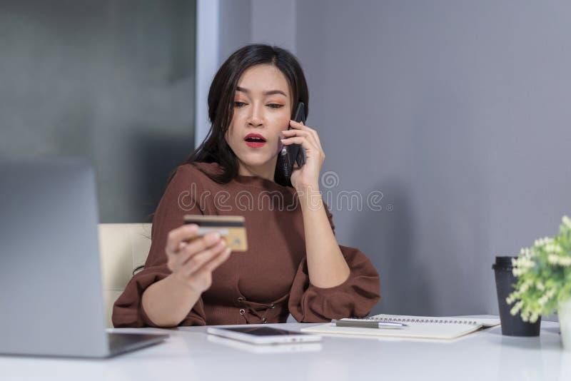 Mulher surpreendida que chama pelo cartão de crédito do telefone e do holdind ao onli foto de stock royalty free