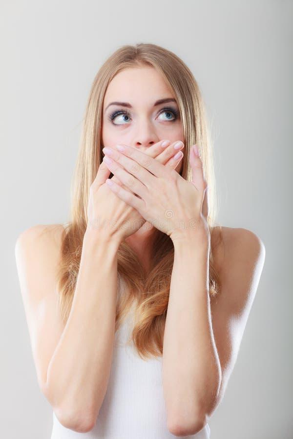 Mulher surpreendida que cobre sua boca com as mãos foto de stock