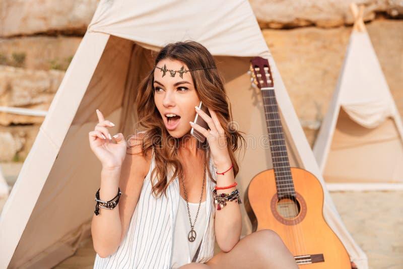 Mulher surpreendida que fala no telefone celular na tenda na praia fotos de stock royalty free