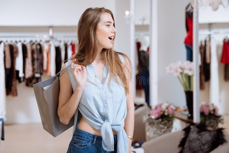 Mulher surpreendida que guarda o saco de compras e a posição na loja de roupa fotografia de stock royalty free