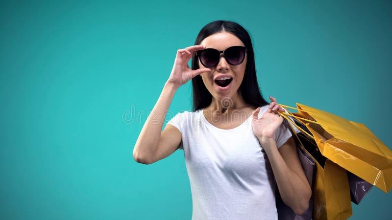 Mulher surpreendida que mantém os óculos de sol e os sacos de papel da compra, olhando descontos foto de stock