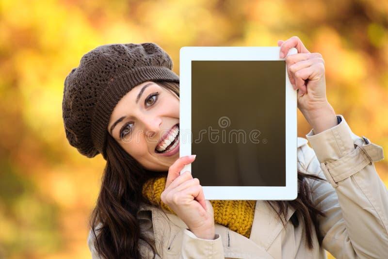 Mulher surpreendida que mostra a tela digital da tabuleta no outono fotos de stock royalty free