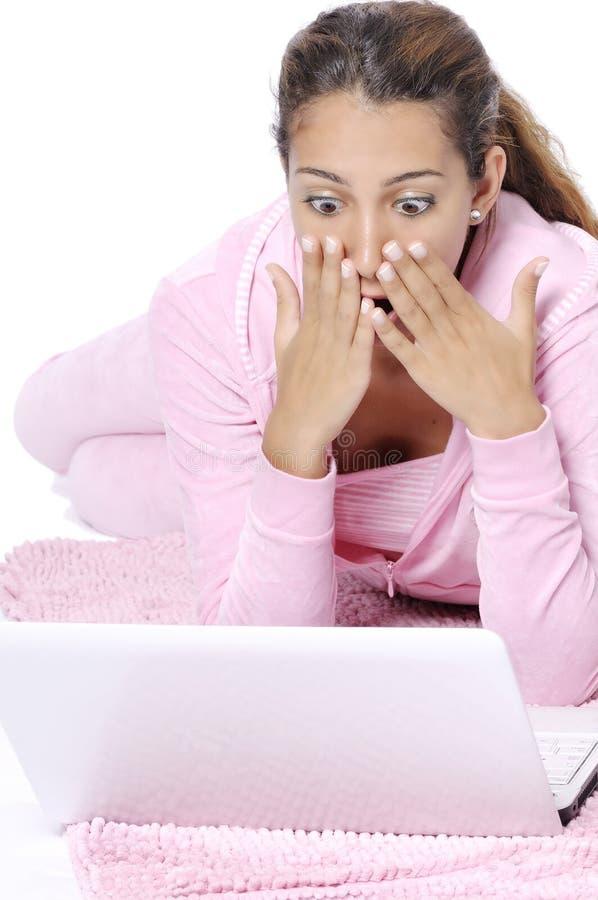 Mulher surpreendida que olha para trás com portátil imagem de stock
