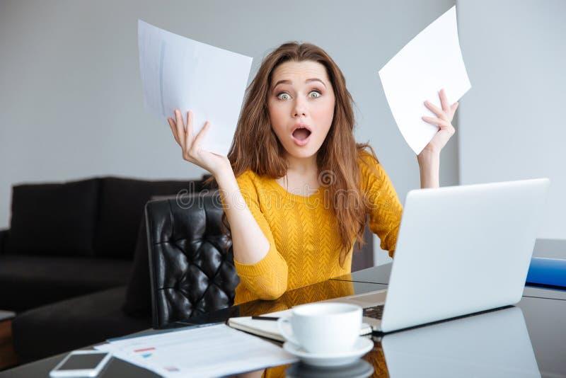 Mulher surpreendida que senta-se na tabela com contas fotografia de stock