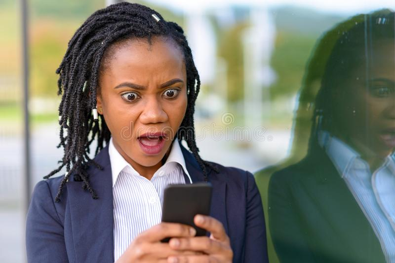 Mulher surpreendida que usa o telefone celular foto de stock royalty free