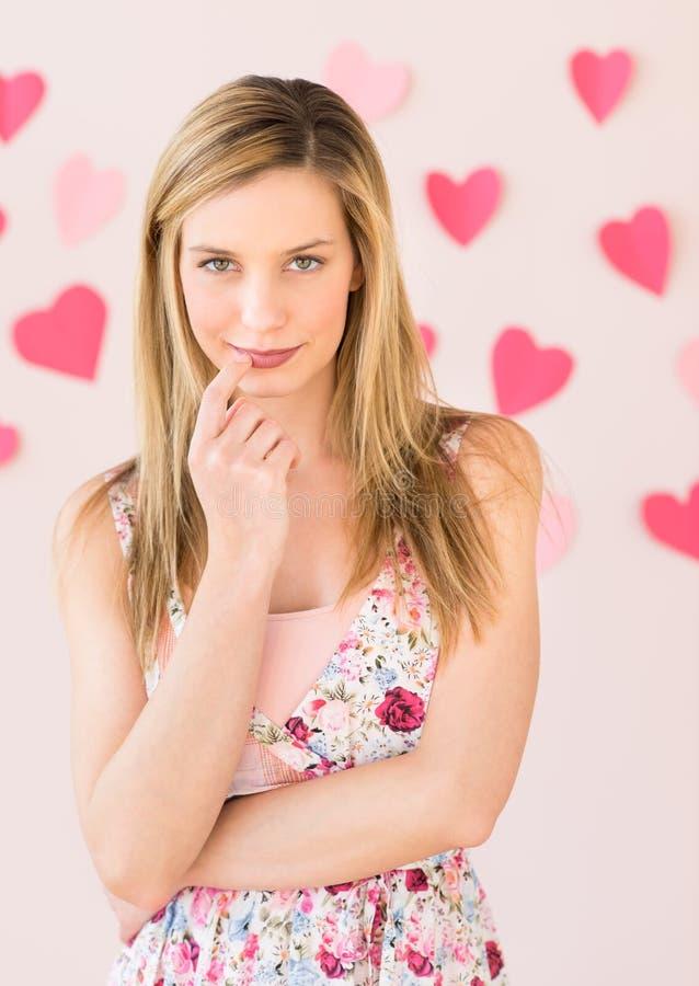Mulher tímida com papéis dados fôrma coração contra o fundo colorido imagem de stock royalty free