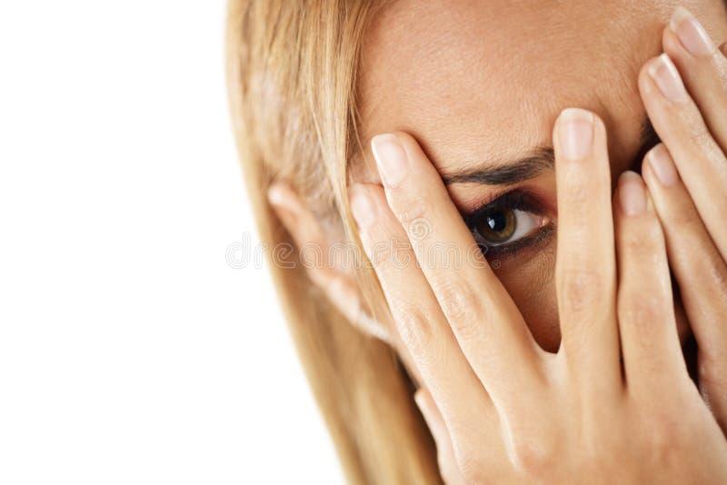 Mulher tímida que olha através dos dedos imagem de stock