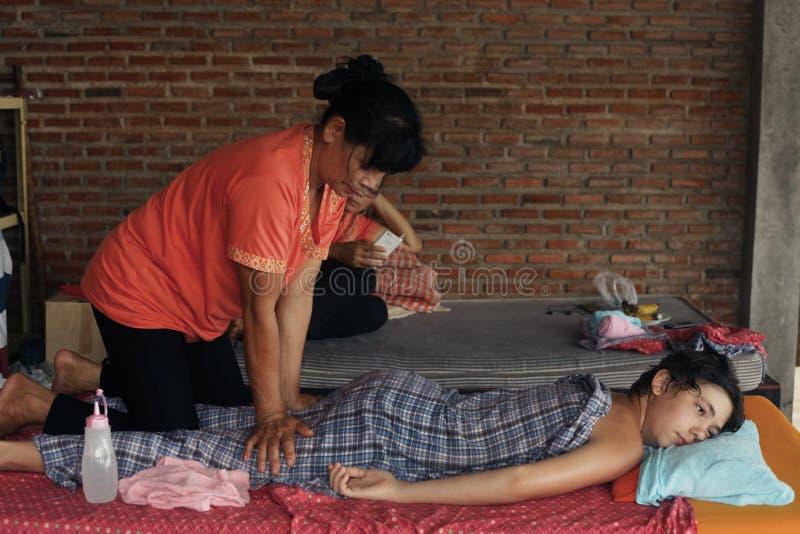 Mulher tailandesa asiática que executa a massagem ao menino europeu do adolescente foto de stock royalty free