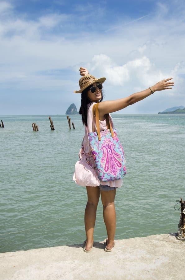 Mulher tailandesa asiática que viaja e que levanta no porto com mar e SK imagens de stock royalty free