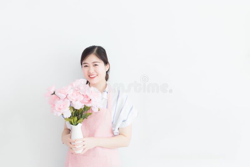 Mulher tailandesa branca, cabelo longo, vestindo um vestido ocasional e um avental cor-de-rosa, guardando um vaso das flores em u fotos de stock