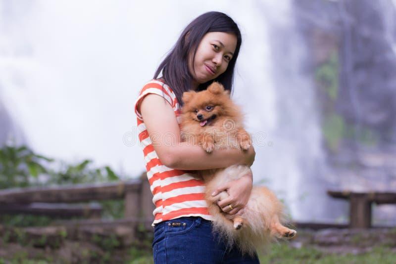 Mulher tailandesa com o pomeranian no chiangmai da cachoeira de Wachirathan foto de stock