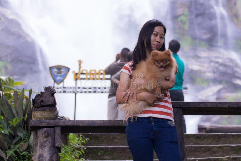 Mulher tailandesa com o pomeranian no chiangmai da cachoeira de Wachirathan foto de stock royalty free