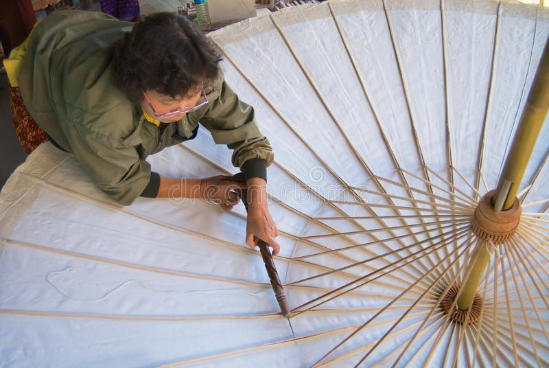 A mulher tailandesa monta o guarda-chuva de bambu tradicional na fábrica em Chiang Mai, Tailândia fotos de stock royalty free