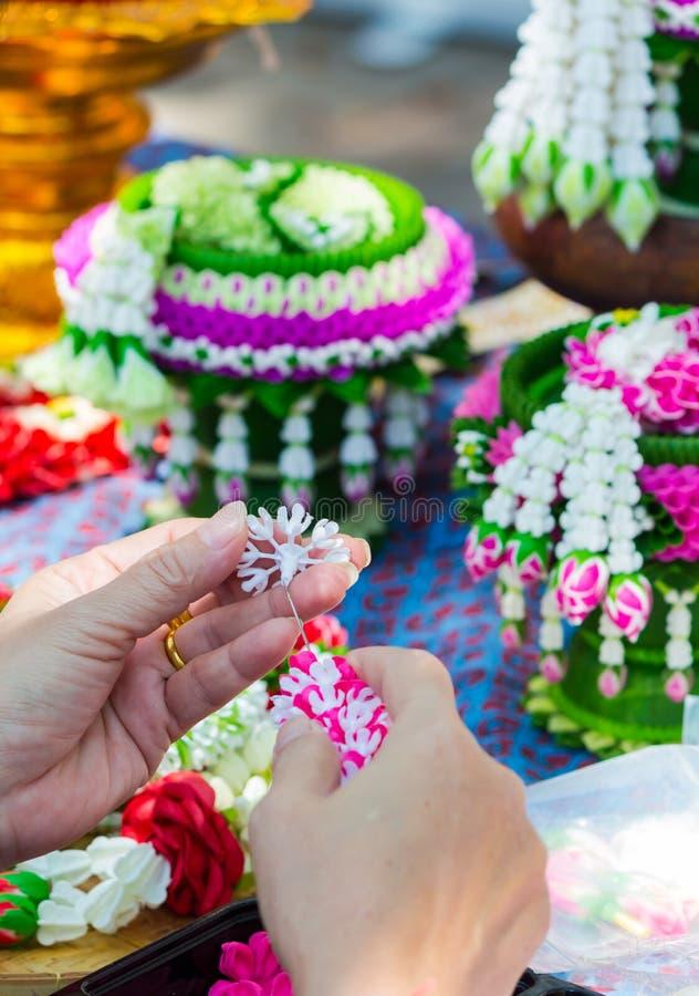 Mulher tailandesa que faz a uma tradição a festão tailandesa das flores fotografia de stock royalty free