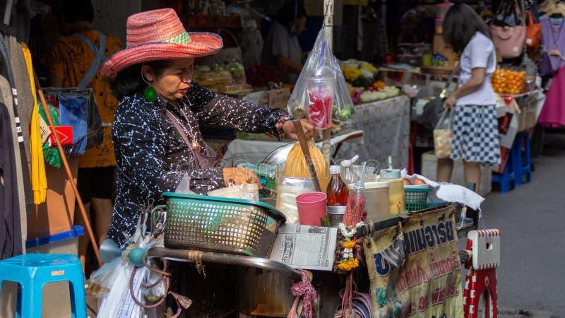 Mulher tailandesa superior que vende o alimento recentemente cozinhado da rua em Wang Lang Market imagens de stock