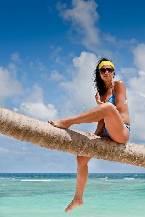 Mulher Tanned que senta-se em uma praia branca da areia da palma fotos de stock royalty free