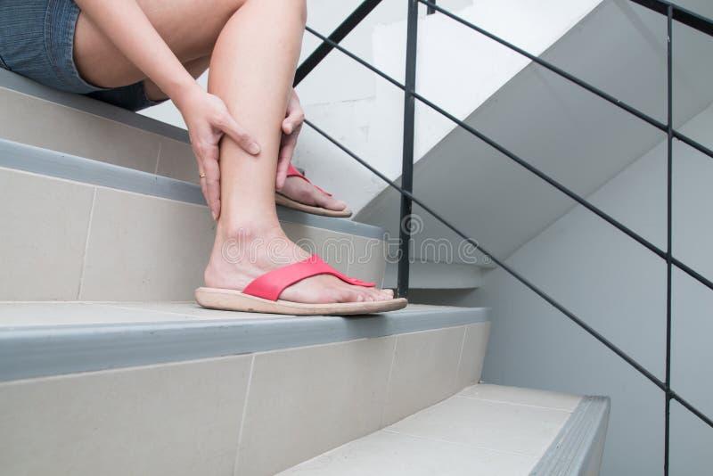 A mulher tem o grampo da vitela e tocando no pé ferido durante vá abaixo das escadas foto de stock