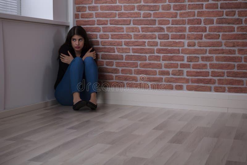 Mulher temida que senta-se no canto imagens de stock