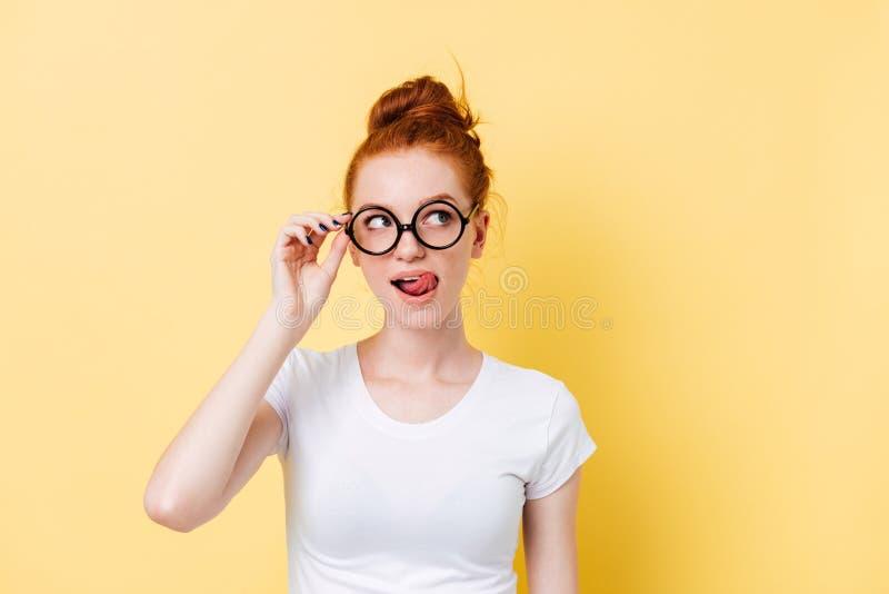 Mulher tentador do gengibre nos monóculos que lambe seus bordos imagem de stock royalty free